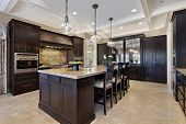 Luxury kitchen in upscale home with dark wood cabinetry poster