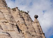 A large boulder balances precariously on a sandstone tapered column in the Tent Rocks National Monument. poster