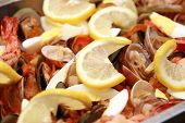 close-up of seafood paella with lots of lemon toppings poster