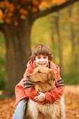 Boy Hugging the Dog in the Fall poster