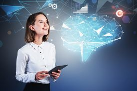 Smiling Young Woman With Tablet Computer Standing Over Blue Background With Holographic Brain Interf
