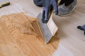 Master Parquet With Spatula In Your Hand. Preparation Of Parquet Grout Material. Mixing Retainer, Va