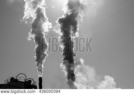 Black And White Rendition Of Clouds Of Smoke Being Emitted Into The Atmosphere By A Sugarcane Refine