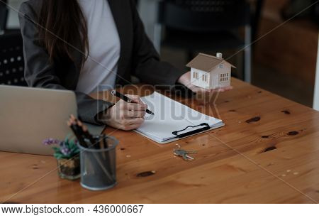Close Up House Model Miniature On Realtor Table, Businesswoman Real Estate Agent Broker Writing With