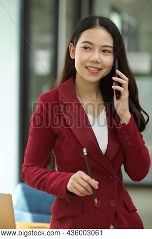 Positive Business Woman In Red Suit Talking On Modern Smart Mobile Phone