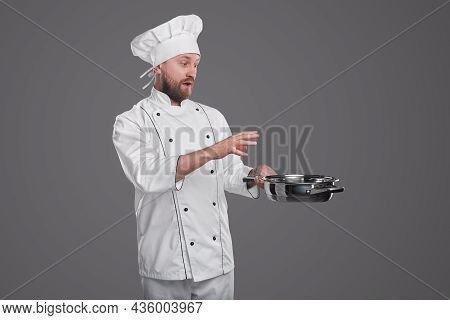 Astonished Male Chef With Beard In Uniform And Toque Standing With Frying Pan On Gray Background