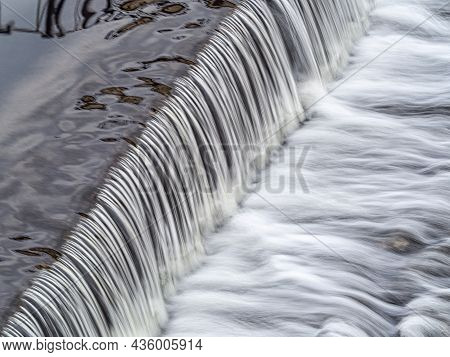 A Small Flat Cascade In A Calm River. Water Background