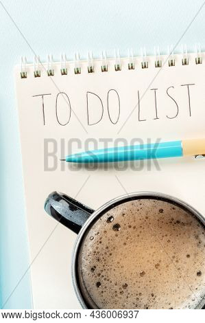 To Do List. A Paper Notebook With A Blue Pen And With Coffee, Shot From The Top On A Blue Background