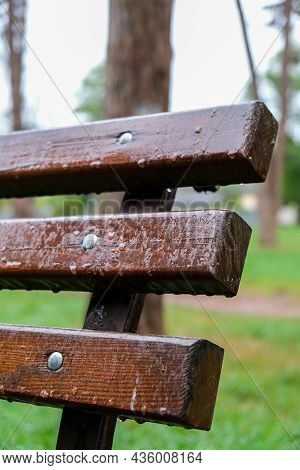 Wet Bench In The Park In The Rain. Rainy Weather. Wooden Chair In The Rain. Wet Urban Furniture. Rai