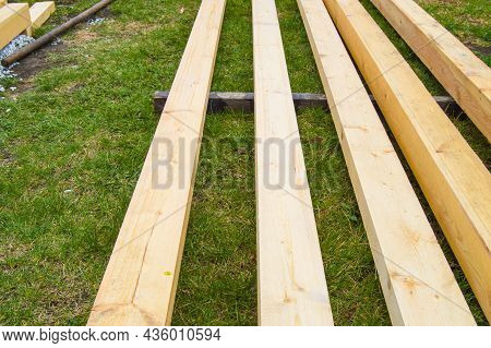 New Wooden Boards On The Grass. Lumber For Suburban Construction