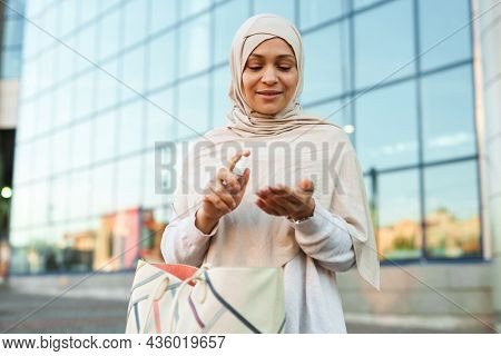 Middle eastern muslim woman in hijab applying sanitizer outdoors