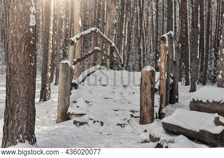 Wooden Little Bridge In A Coniferous Forest Covered With Snow On Winter Day