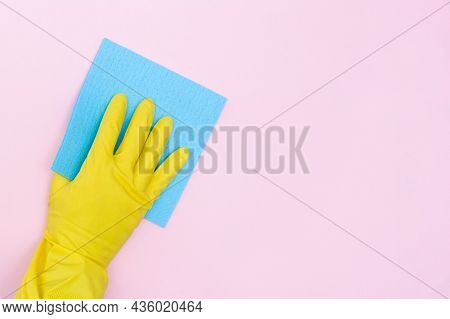 Man In Rubber Gloves Holds A Yellow Rag On A Pink Background. Isolated. Rubber Gloves For Cleaning A
