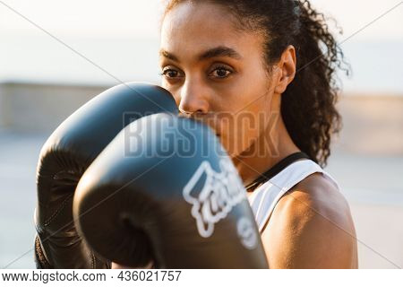 Black sportswoman boxing while working out outdoors