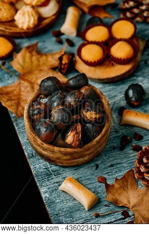 closeup of some roasted chestnuts in a wooden bowl and some different confections eaten in Spain on All Saints Day, such as Panellets, Huesos de Santo or Yemas de Santa Teresa on a gray rustic table