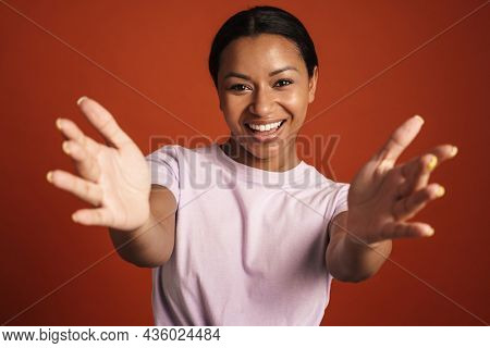 Young black woman smiling and reaching out her hands at camera isolated over red wall
