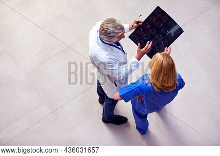 Overhead Shot Of Male Doctor Wearing White Coat Discussing Scan With Female Colleague In Scrubs
