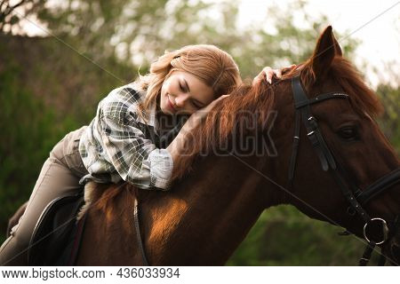 Woman With Long Hair Posing With A Brown Horse In A Forest In A Sunny Meadow.