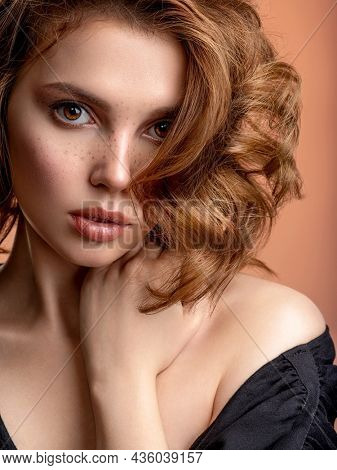 Beautiful young woman with freckles on face.  Closeup portrait of an attractive girl  with a brown makeup.  Beautiful brown haired with stylish short hairstyle. Woman with a  curly hair.