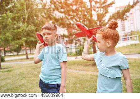 Little Girl And Boy With Airplane Toys. Adventure Fly Concept. Stay Home Game. Family Garden Activit