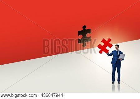 Businessman putting missing jigsaw puzzle piece