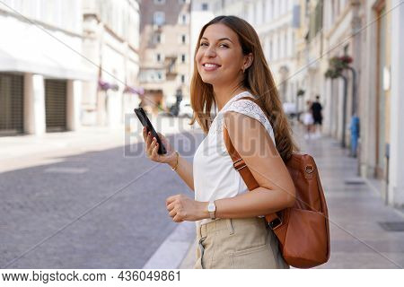 Pretty Young Woman Walking In City Street While Holding The Smartphone And Looking Sideways