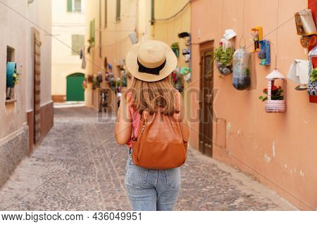 Tourism In Alghero, Sardinia. Back View Of Traveler Girl Walking In Picturesque Cozy Narrow Alley Of