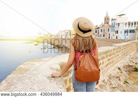 Summer Holiday In Italy. Back View Of Young Woman With Hat And Backpack In Alghero, Old Town, Sardin