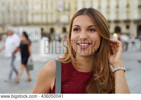 Close Up Shot Of Young Beautiful Surprised Woman Looks Away Against City Blurred Background
