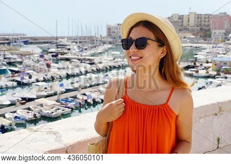Portrait Of Cheerful Smiling Woman With Orange Dress Walking On Promenade Of Bisceglie Port, Apulia,