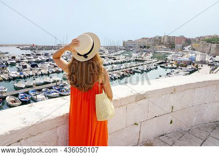 Rear View Of Woman With Orange Dress Looking Bisceglie Port From The Old Town, Apulia, Italy