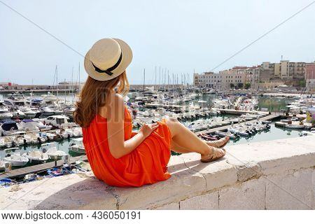 Beautiful Young Woman With Hat And Summer Dress Sitting On Wall Looking The Port Of Bisceglie, Apuli