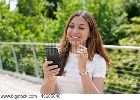 Beautiful Young Casual Woman Sending Text Message On Mobile Phone In City Park