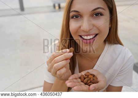 Close Up Of Pretty Healthy Girl Eating Almonds In Break Time Outdoor. Healthy Food Concept. Copy Spa