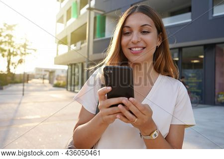 Young Attractive Woman Using Smartphone In City At Sunset