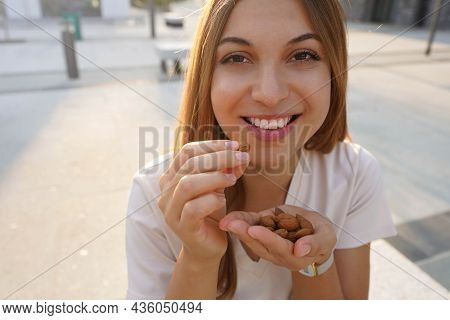 Close Up Of Healthy Girl Eating Almonds In Break Time Outdoor. Healthy Food Concept.