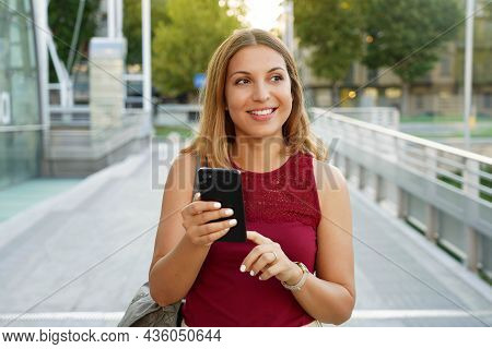 Smiling Young Woman Is Walking In The Street With Phone. She Is Holding Gadget In Hand And Looking A