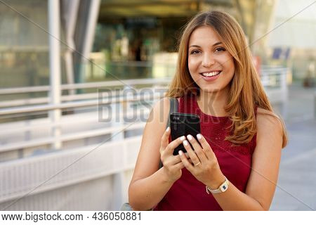 Brazilian Girl Using Smartphone Near Metro Station. Cheerful Young Woman Chatting With Mobile Phone