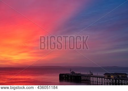 Soft Glowing Twilight, Sunrise Sky In Orange, Yellow And Magenta Colors With Sea And Pier.
