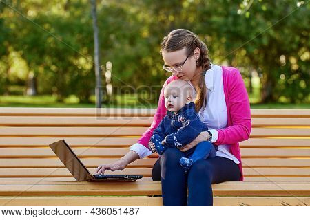 Woman Is Sitting In Park With Infant During Teleworking With Laptop.
