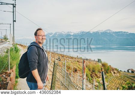 Middle Age Man Hiking With Backpack, Posing Next To Railways With Lake Geneva And Haute-savoie View,