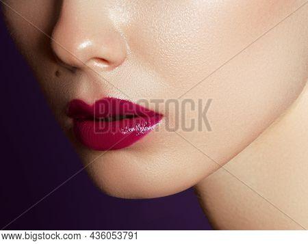 Close Up View Of Beautiful Woman Lips With Purple Matte Lipstick. Cosmetology, Drugstore Or Fashion