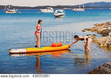 Older Teenage Girl Helps Little Sister Go To Sea On Sup Board - Leisure Time Concept