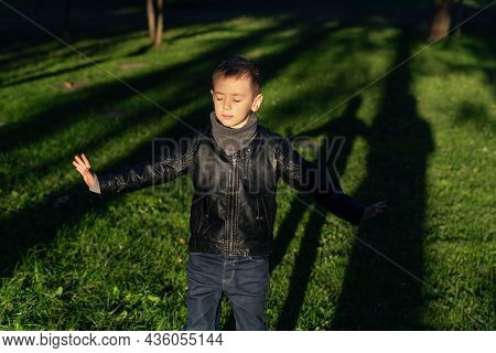 Emotive Portrait Of A Preschooler Boy With His Arms Open And Eyes Closed. A Little Child Enjoying Th