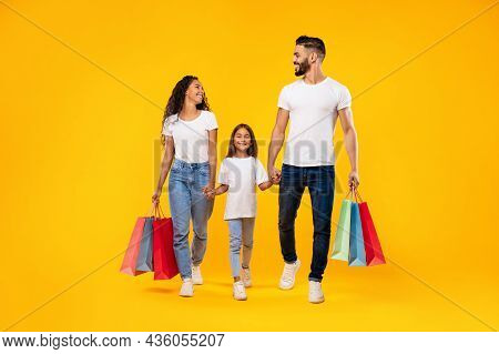 Middle-eastern Family Shopping Carrying Shopper Bags Walking Over Yellow Background