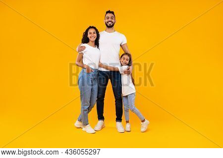 Middle-eastern Parents And Daughter Embracing Expressing Positive Emotions, Yellow Background