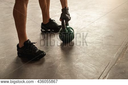 Crop Anonymous Male In Sneakers And Weightlifting Gloves Bending Forward And Preparing To Lift Heavy