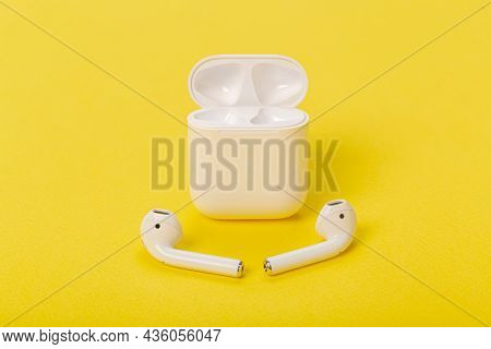 Wireless Bluetooth Headphones With Charging Case On A Yellow Background. The Concept Of Modern Techn
