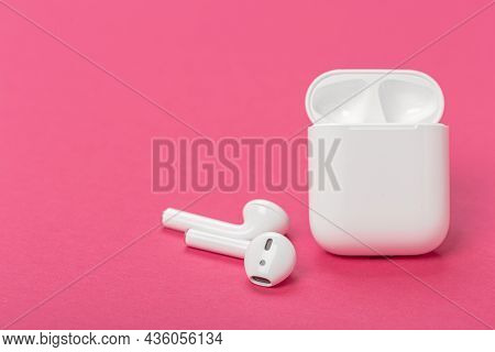 Modern Wireless Bluetooth Headphones With Charging Case On Pink Background. The Concept Of Modern Te