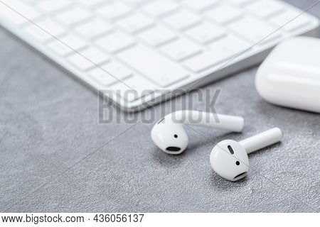 Modern Wireless White Bluetooth Headphones With Charging Case Near Bluetooth Keyboard On Gray Table